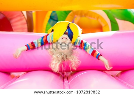 Child jumping on colorful playground trampoline. Kids jump in inflatable bounce castle on kindergarten birthday party Activity and play center for young child. Little boy playing outdoors in summer. #1072819832