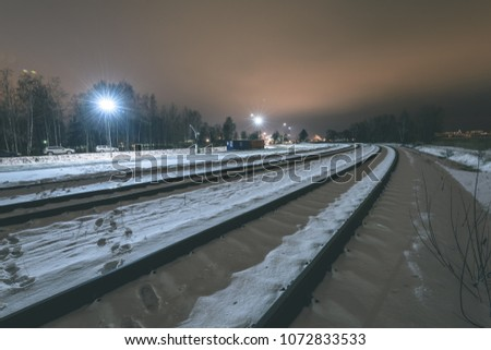 Night photography long exposure. Riga, Latvia industrial port details over frozen river of Daugava. railroad tracks - vintage retro look #1072833533