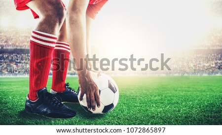 red team soccer footballer get the ball to free kick or penalty kick during match in the stadium Royalty-Free Stock Photo #1072865897