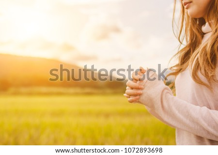 Soft Focus,A young woman praying for God's blessings with the power and power of the sacred On the background of sunrise in the morning over a golden meadow. The concept of God and spirituality. #1072893698