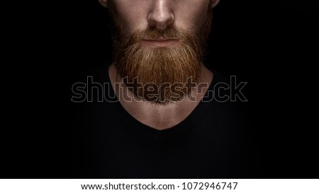 Perfect beard. Close-up of young bearded man standing against black background #1072946747