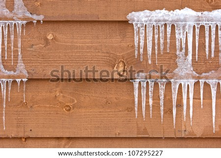 Icicles hang from a wood cabin on a chilly winter day Royalty-Free Stock Photo #107295227