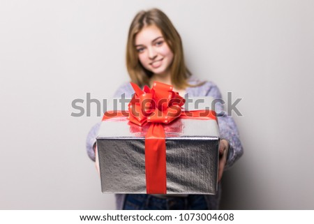 Adorable teenage girl looking at box with present