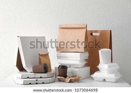 Assortment of food delivery containers on white table #1073064698