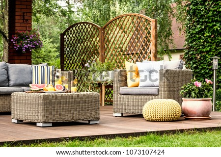 Grapefruit and orange juice on the table on wooden terrace with yellow pouf next to armchair #1073107424