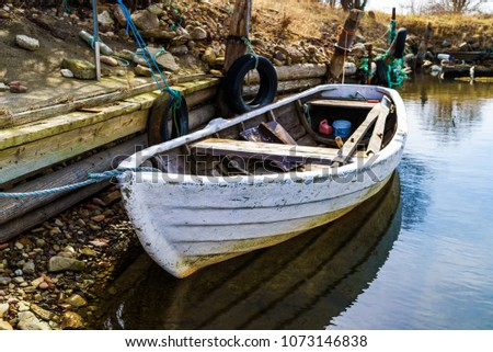White rowboat tied to a pier on a sunny day. #1073146838