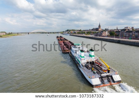 Cargo riverboat passing the Dutch city Nijmegen on the river Waal #1073187332