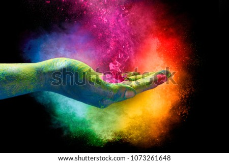 Holi festival concept. Magical rainbow colored powder exploding from the palm of a cupped hand creating a vibrant cloud of dust in the colors of the spectrum over a black background.  #1073261648