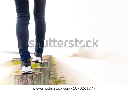 A woman walking on stump carefully next to the road. Concept of living life with confidence and take care every steps of moving forward to make sure life safe. Free copied space for text on right. #1073261777