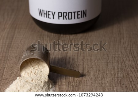 Whey protein food supplement for training and exercise. Dropped scoop with vanilla powder flavour. Wooden table. Black jar behind #1073294243