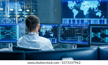 Back View in the System Control Center Operator Working. Multiple Screens Showing Technical Data. Royalty-Free Stock Photo #1073337962