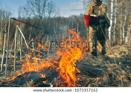 Firefighter. Burning Grass. Fireman at work. Liquidation of a fire. Firefighting, scorched earth. Forest fires. Fire safety. Firefighter in protective suit. Fire prevention #1073357162