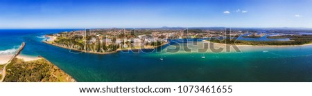 Port Macquarie regional town in NSW, Australia, on Mid North Coast at the river mouth of Hastings river in to Pacific ocean. Aerial wide panorama of town riverfront around downtown and wharf. #1073461655