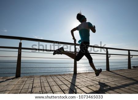Sporty fitness female runner running on seaside boardwalk during sunrise #1073465033