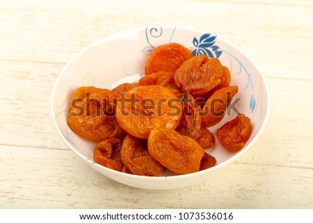 Dried apricots heap in the bowl over wooden background #1073536016
