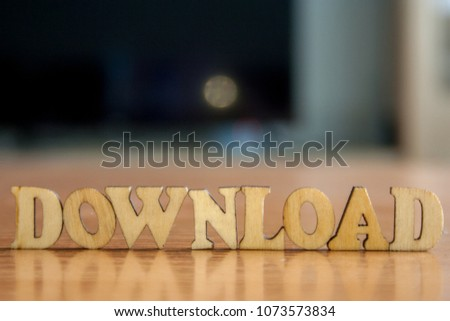 The word 'download' made of wooden letters. wood inscription on table