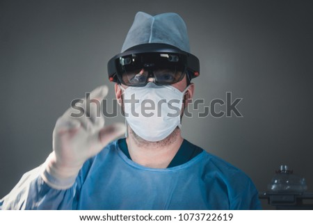 Surgeon using augmented reality holographic hololens glasses while operating in modern operation theater #1073722619