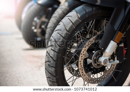 Motorbike parking in row in city street. Close up of wheel. shallow focus.