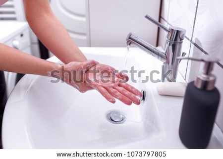 Hand cleaning with antibacterial soap in bathroom under running water Close up