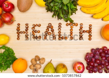 Flat lay of arranged hazelnuts in word Health surrounded with plenty of healthy fresh fruit and gree on wood. #1073857862