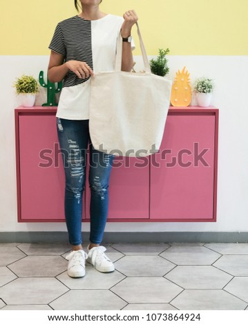 woman showing white totebag. Tote bag mock up for designer. In fun background, pink yellow and green pallete #1073864924