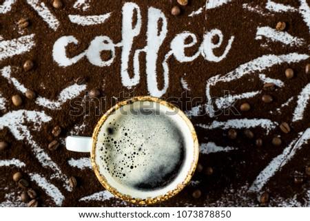 """A cup of fresh hot coffee with foam next to the word """"coffee"""" written on the ground coffee #1073878850"""