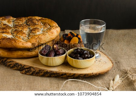 Iftar meal (time to break the fast) with sweet dry dates,apricot,black olives,water and Ramadan bread on the wooden board.Beginning meal before main menu. #1073904854