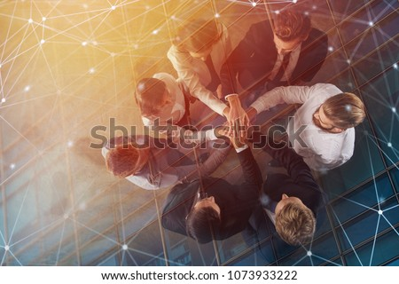Business people putting their hands together with internet network effects. Concept of integration, teamwork and partnership. double exposure #1073933222
