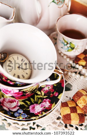 Close up porcelain cap with pocket watch and biscuits