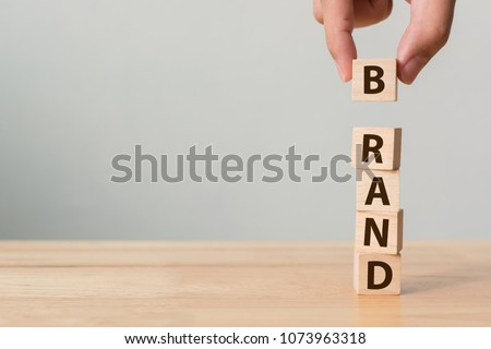 Hand of male putting wood cube block with word BRAND on wooden table. Brand building for success concept Royalty-Free Stock Photo #1073963318