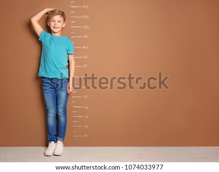 Little boy measuring his height near color wall #1074033977