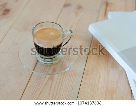 Espresso in glass on wooden table with magazing in the morning #1074137636