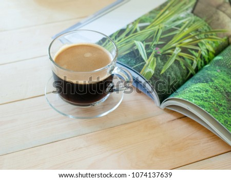Fresh coffee in glass on wooden table with magazing in the morning #1074137639