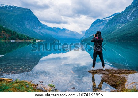 Nature photographer tourist with camera shoots Beautiful Nature Norway natural landscape. lovatnet lake. #1074163856