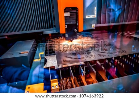 CNC Laser cutting of metal, modern industrial technology. Small depth of field. Warning - authentic shooting in challenging conditions. #1074163922