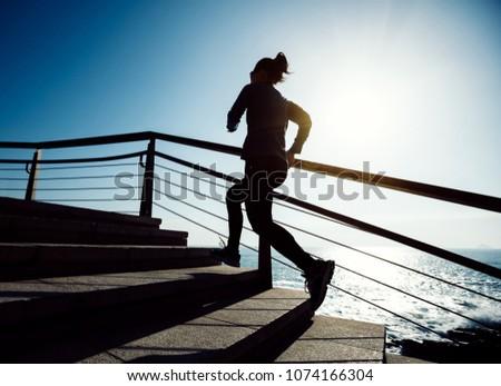 sporty female runner running upstairs on coast trail #1074166304