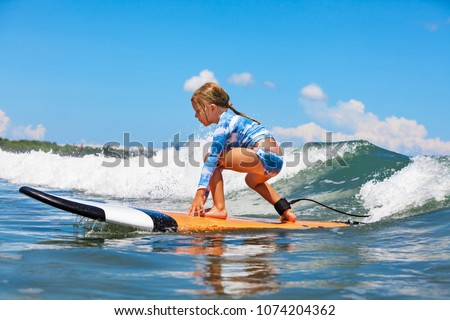 Happy baby girl - young surfer ride on surfboard with fun on sea waves. Active family lifestyle, kids outdoor water sport lessons and swimming activity in surf camp. Summer vacation with child. #1074204362