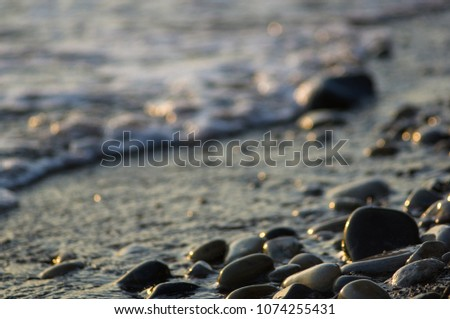 pebble stones on the sea beach, the rolling waves of the sea with foam #1074255431