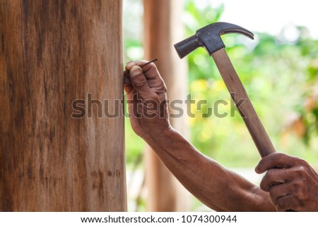 The carpenter is repairing the house. He makes nails using a hammer  #1074300944