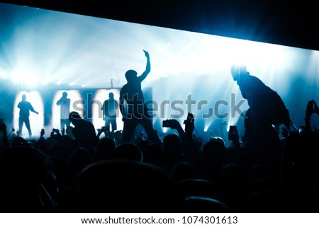People in the concert crowd stands on the shoulders. Performing band in the background. Blue illumination. #1074301613