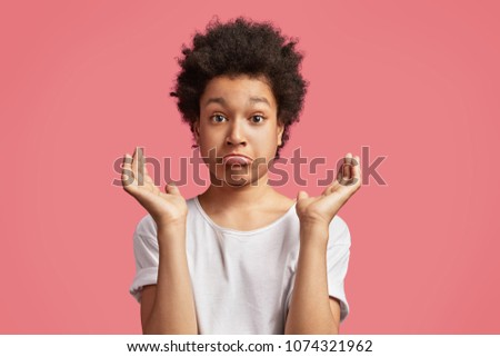 Puzzled handsome mixed race teenager with Afro hairstyle, cuves lower lip and gestures in bewilderment, express uncertainty, wears casual white t shirt, isolated over pink background. Children concept #1074321962
