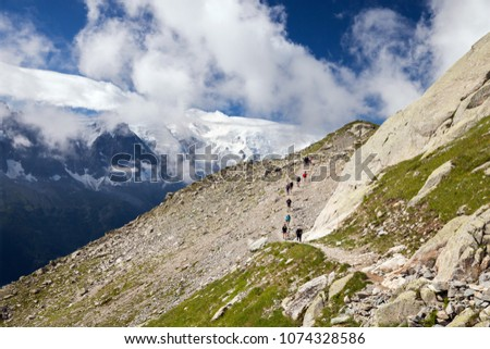 Tourists are walking on mountaing trail in summer day with view on Mont Blanc, France #1074328586