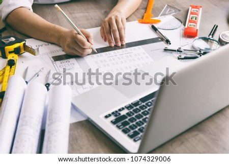 Architect hands working on blueprint plans  with  a pencil,  a ruler, calculator, smartphone, laptop and engineering tools #1074329006