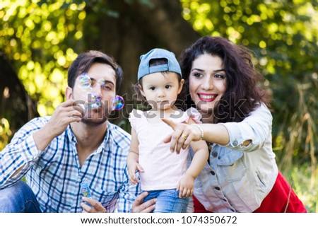 Family fun in nature. Happy mom, dad and daughter blow bubbles in the park. #1074350672