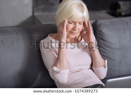 Mature elderly ill woman having headache sitting in the room on the sofa and holding hands by head. #1074389273