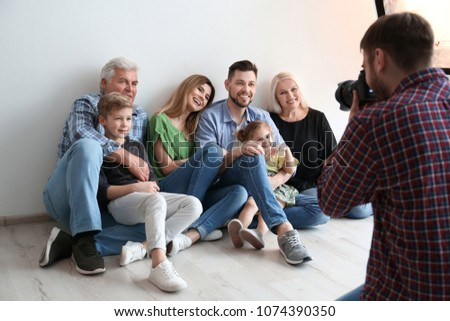 Professional photographer taking photo of family in studio #1074390350