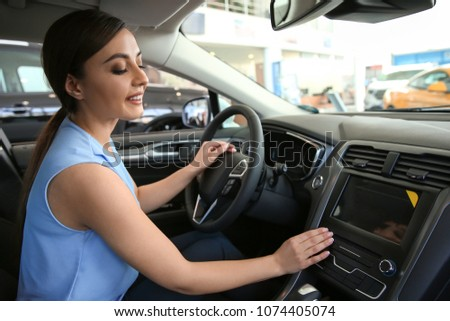 Young woman sitting in driver's seat of new car at salon #1074405074
