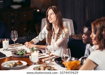 Two european women and african guys sitting at the table served for dinner and talking, enjoying their time together #1074459629