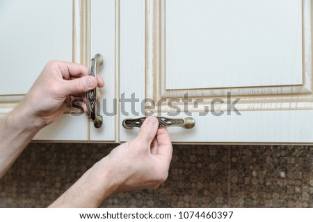 Installation of kitchen furniture. A man is putting handles to door cabinets. #1074460397