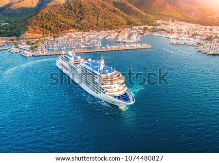 Cruise ship at harbor. Aerial view of beautiful large white ship at sunset. Landscape with boats, mountains, sea, blue sky. Top view of yacht. Luxury cruise. Floating liner in Europe. Travel. Resort #1074480827